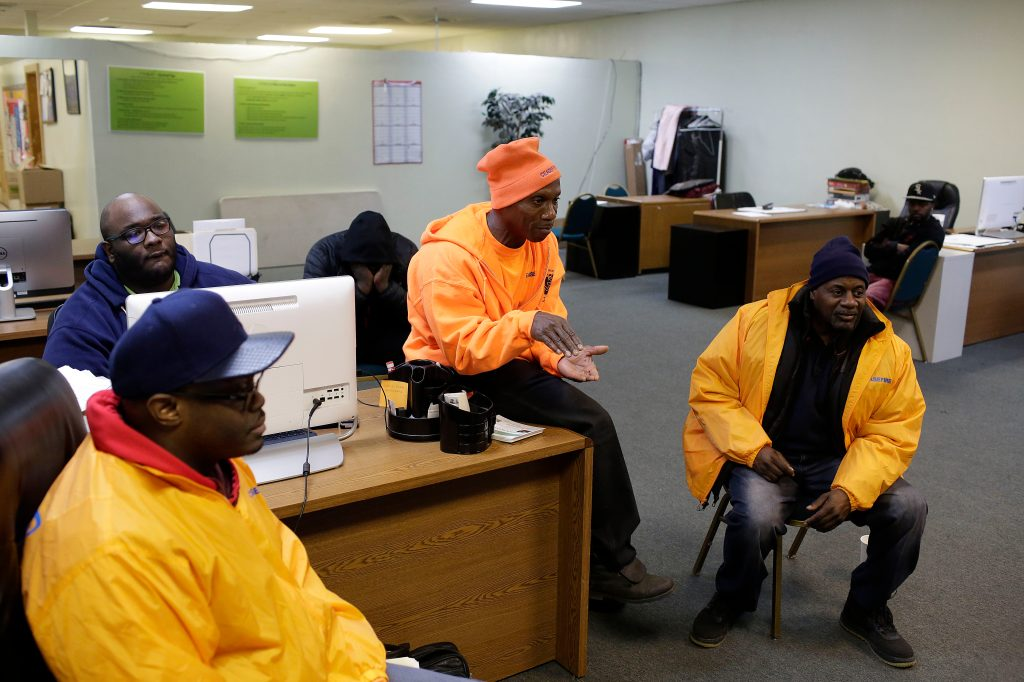 Violence interrupters Charles Jones (left), Joewaine Washington (center), and Thomas Jefferson (right), plan a patrol at the Target Center in Englewood. (Photo by Joshua Lott for The Trace)